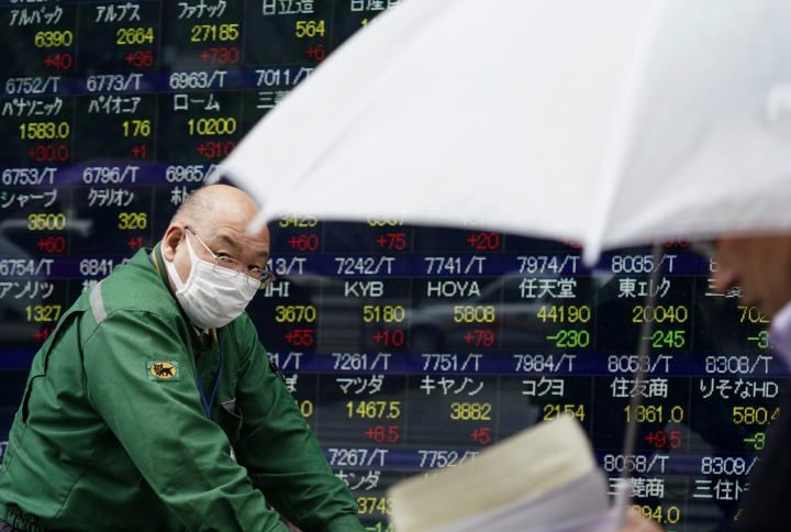 People walk past an electronic stock indicator of a securities firm in Tokyo, Wednesday, April 18, 2018. Asian stock markets followed Wall Street higher on Wednesday after Beijing added to a swelling trade dispute with Washington by hiking tariffs on U.S. sorghum. (AP Photo/Shizuo Kambayashi)