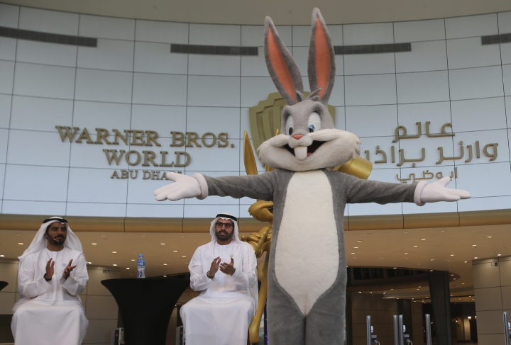 Mohamed Khalifa al-Mubarak, the chairman of both Miral and Abu Dhabi's Department of Culture and Tourism, second left, claps for a Bugs Bunny character during a news conference organized by the Warner Bros. World amusement park, in Abu Dhabi, United Arab Emirates, Wednesday, April 18, 2018. Abu Dhabi will open the $1 billion indoor amusement park this July, officials announced Wednesday, the latest offering in a crowded market in the United Arab Emirates where one marquee park already faces serious financial problems. (AP Photo/Kamran Jebreili)