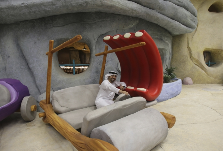 An Emirati poses with Fred Flintstone's mock-up car at the Warner Bros. World amusement park in Abu Dhabi, United Arab Emirates, Wednesday, April 18, 2018. Abu Dhabi will open a $1 billion indoor Warner Bros. amusement park this July, officials announced Wednesday, the latest offering in a crowded market in the United Arab Emirates where one marquee park already faces serious financial problems. (AP Photo/Kamran Jebreili)
