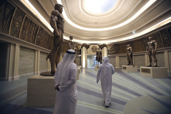 Emirati officials look at statues of members of the Justice League, a comic book series, at the Warner Bros. World amusement park in Abu Dhabi, United Arab Emirates, Wednesday, April 18, 2018. Abu Dhabi will open a $1 billion indoor Warner Bros. amusement park this July, officials announced Wednesday, the latest offering in a crowded market in the United Arab Emirates where one marquee park already faces serious financial problems. (AP Photo/Kamran Jebreili)