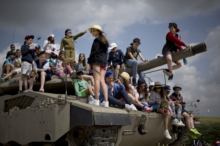 FILE - In this April 22, 2015 file photo, school children from Belgium sit on a tank as they listen to an Israeli soldier speak about Israel's wars, at the wall of names of fallen soldiers, at the Armored Corps memorial in Latrun. As Israel marks the 70th anniversary of statehood starting at sundown Wednesday, April 18, 2018, satisfaction over its successes and accomplishments share the stage with a grim disquiet over the never-ending conflict with the Palestinians, internal divisions and an uncertain place in a hostile region. (AP Photo/Ariel Schalit, File)