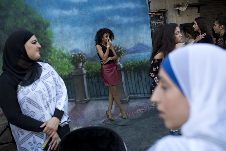FILE - In this Sept. 12, 2016 file photo, an Israeli Arab youth has her photo taken by a photographer during a parade for the Muslim Eid al-Adha holiday, in the mixed Arab Jewish neighborhood of Jaffa, near Tel Aviv, Israel. As Israel marks the 70th anniversary of statehood starting at sundown Wednesday, April 18, 2018, satisfaction over its successes and accomplishments share the stage with a grim disquiet over the never-ending conflict with the Palestinians, internal divisions and an uncertain place in a hostile region. (AP Photo/Oded Balilty, File)