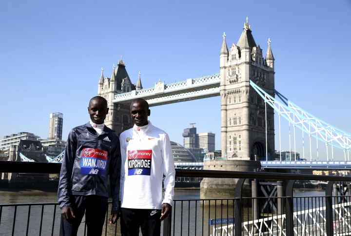 Kenya's Daniel Wanjiru, left, and Eliud Kipchoge pose for a picture in front of Tower Bridge during the media day at the Tower Hotel, London, Thursday, April 19, 2018. London marathon will be raced Sunday. (Steven Paston/PA via AP)