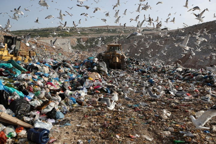 """FILE - In this Wednesday, Feb. 2, 2018 file photo, earthmovers push mountains of garbage as seagulls fly over the country's largest landfill at Fyli on the outskirts of Athens. The British government is planning a consultation about a possible bill to end the use of plastic straws, drink stirrers and cotton buds - and is urging other Commonwealth nations to ban the practice as well. Prime Minister Theresa May said Thursday, April 19, 2018 that """"plastic waste is one of the greatest environmental challenges facing the world."""" (AP Photo/Thanassis Stavrakis, file)"""