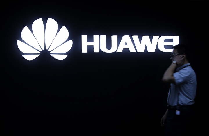 In this May 26, 2016, photo, a man walks past a Huawei logo during a launch event for the Huawei Matebook in Beijing. As trade disputes simmer, Chinese telecommunications giant Huawei, the No. 3 smartphone brand, is shifting its growth efforts toward Europe and Asia in the face of mounting obstacles in the U.S. market. (AP Photo/Mark Schiefelbein)