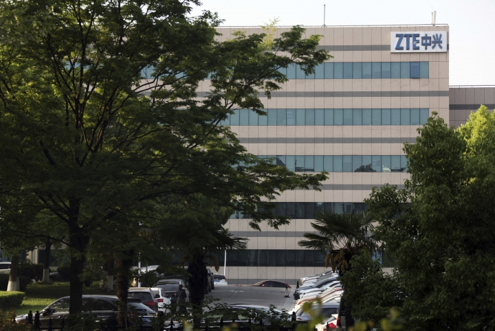 "In this April 17, 2018, photo, a woman walks through the parking lot of a building hosting ZTE subsidiaries in Nanjing in eastern China's Jiangsu province. Chinese tech company ZTE said Friday, April 20, 2018, that it won't accept an ""unfair"" U.S. penalty in a case involving exports of telecoms equipment to North Korea and Iran and is seeking a solution through legal channels. (Chinatopix via AP)"