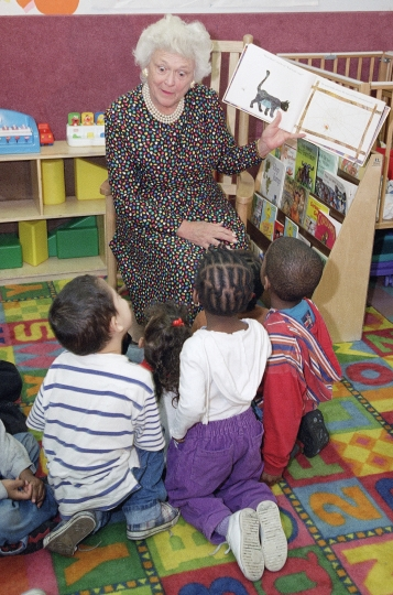 """FILE - In this May 16, 1994 file photo, former first lady Barbara Bush reads to a group of children at the Clinton Family Inn, a shelter run by Homes for the Homeless in New York. Promoting literacy was a longtime cause for Barbara Bush, who died Tuesday, April 17, 2018, at age 92. She met many authors during her time in Washington and in the years following. Sandra Brown, Mary Higgins Clark and Harlan Coben were among those who became good friends, and shared memories of a former first lady whom Brown said """"put her heart and soul"""" into getting people to read while also being """"very funny, very candid with her comments."""" (AP Photo/Luc Novovitch, File)"""