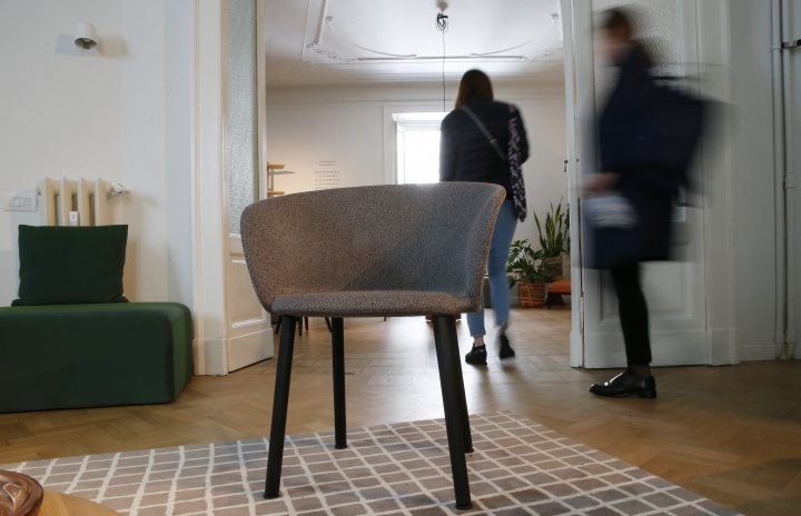 """People walk past a """"Burgundy"""" chair by Kendo, during the first day of the Design Week, in Milan, Italy, Tuesday, April 17, 2018. The Milan Design week is taking place in various locations across Milan from April 17 through 22, 2018. (AP Photo/Antonio Calanni)"""
