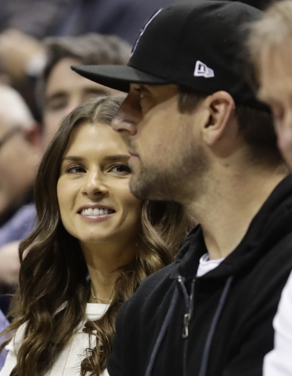 Danica Patrick talks to Green Bay Packers' Aaron Rodgers during the first half of Game 3 of an NBA basketball first-round playoff series between the Milwaukee Bucks and the Boston Celtics Friday, April 20, 2018, in Milwaukee. (AP Photo/Morry Gash)