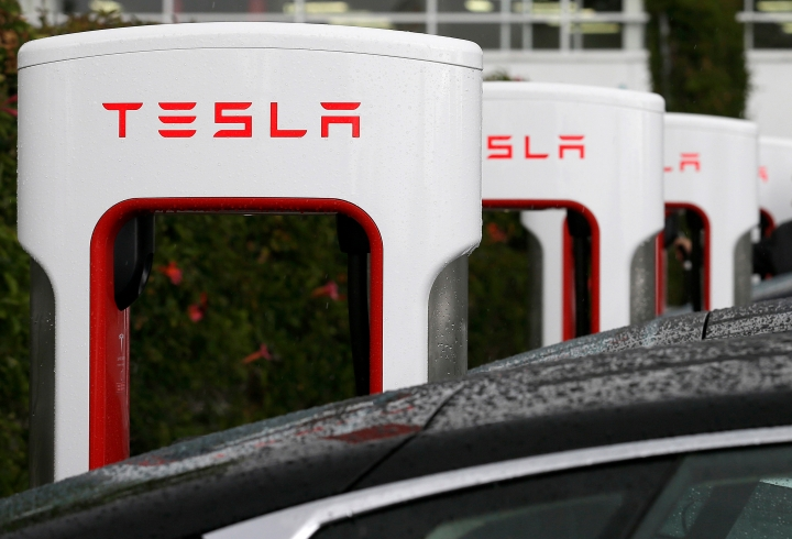 FILE - In this May 14, 2015, file photo, Tesla charging stations are shown outside of the Tesla factory in Fremont, Calif. California workplace safety regulators say they are investigating two incidents at automaker Tesla's factory. The investigations follow a report by the Center for Investigative Reporting cataloguing a series of workplace injuries at Tesla. Tesla said the center incorrectly counted injuries that occurred away from the factory in Fremont. (AP Photo/Jeff Chiu, File)