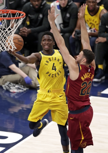 Indiana Pacers guard Victor Oladipo (4) shoots around Cleveland Cavaliers forward Larry Nance Jr. (22) during the first half of Game 3 of an NBA basketball first-round playoff series in Indianapolis, Friday, April 20, 2018. (AP Photo/Michael Conroy)