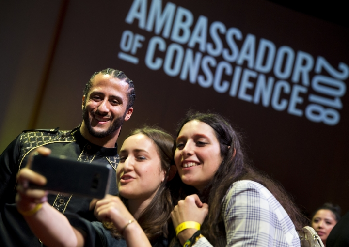 Former NFL quarterback and social justice activist Colin Kaepernick poses with guests after receiving the Amnesty International Ambassador of Conscience Award for 2018 in Amsterdam, Saturday April 21, 2018. Kaepernick became a controversial figure when refusing to stand for the national anthem, instead he knelt to protest racial inequality and police brutality. (AP Photo/Peter Dejong)