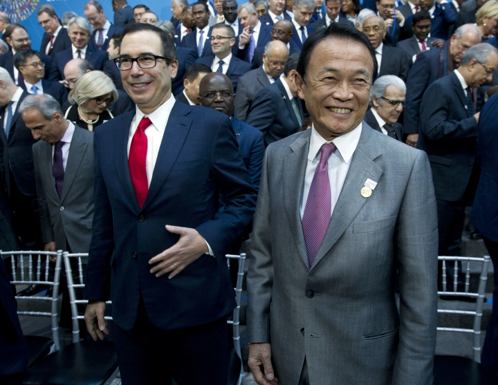 U.S. Treasury Secretary Steve Mnuchin, left, and Japan's Finance Minister Taro Aso attend the International Monetary Fund (IMF) Governors group photo at World Bank/IMF Spring Meetings, in Washington, Saturday, April 21, 2018. (AP Photo/Jose Luis Magana)