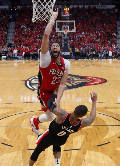 New Orleans Pelicans forward Anthony Davis (23) goes to the basket over Portland Trail Blazers guard Damian Lillard (0) during the second half of Game 4 of a first-round NBA basketball playoff series in New Orleans, Saturday, April 21, 2018. The Pelicans won 131-123 to sweep the series. (AP Photo/Scott Threlkeld)