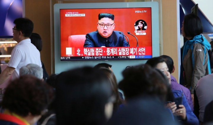 """FILE - In this April 21, 2018 file photo, people watch a TV screen showing an image of North Korean leader Kim Jong Un during a news program at the Seoul Railway Station in Seoul, South Korea. The signs read: """"North Korea says it has suspended nuclear tests."""" North Korea's abrupt diplomatic outreach in recent months comes after a flurry of weapons tests that marked 2017, including the underground detonation of an alleged thermonuclear warhead and three launches of developmental ICBMs designed to strike the U.S. mainland. Inter-Korean dialogue resumed after Kim in his New Year's speech proposed talks with the South to reduce animosities and for the North to participate in February's Winter Olympics in Pyongchang. North Korea sent hundreds of people to the games, including Kim's sister, who expressed her brother's desire to meet with Moon for a summit. South Korean officials later brokered a potential summit between Kim and Trump. (AP Photo/Ahn Young-joon, File)"""