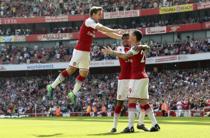 Arsenal's Nacho Monreal, left, celebrates scoring his side's first goal of the game with team mates during the English Premier League soccer match against West Ham United at the Emirates Stadium in London, Sunday April 22, 2018. (Mark Kerton/PA via AP)