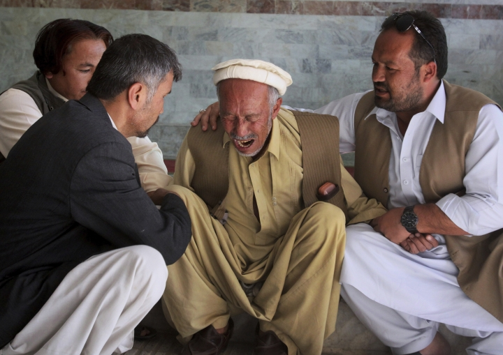 People comfort a man who lost his son in a deadly shooting incident outside a hospital in Quetta, Pakistan, Sunday, April 22, 2018. Police in Pakistan said gunmen have killed multiple Shiites, the latest in a recent series of attacks on the religious minority. (AP Photo/Arshad Butt)