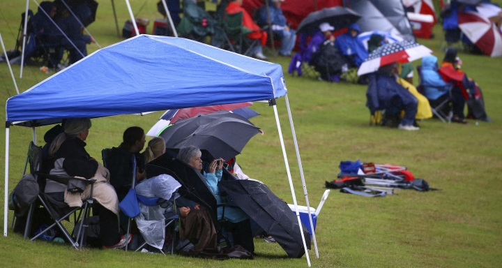 Fans watch from under tents and umbrellas as rain falls during the Honda Indy Grand Prix of Alabama auto race at Barber Motorsports Park, Sunday, April 22, 2018, in Birmingham, Ala. (AP Photo/Butch Dill)