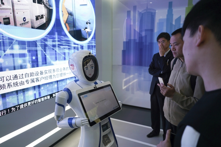 "In this April 13, 2018, photo, bank customers speak with a robot at an automated branch in Shanghai. The outlet opened by Beijing-based China Construction Bank has been dubbed China's first ""unmanned bank"" and is equipped with face-scanning software, a virtual reality room and talking robots. (AP Photo/Dake Kang)"