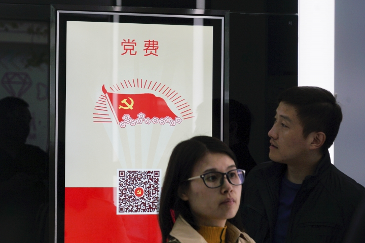 """In this April 13, 2018, photo, a bank customer looks at a touchscreen which allows users to pay Communist Party membership fees at an automated branch in Shanghai. The outlet opened by Beijing-based China Construction Bank has been dubbed China's first """"unmanned bank"""" and is equipped with face-scanning software, a virtual reality room and talking robots. (AP Photo/Dake Kang)"""