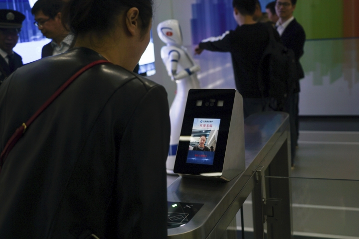 "In this April 13, 2018, photo, a China Construction Bank employee demonstrates the use of face-scanning software at an automated bank in Shanghai. The outlet opened by the Beijing-based bank has been dubbed China's first ""unmanned bank"" and is equipped with holograms, a virtual reality room and talking robots. (AP Photo/Dake Kang)"