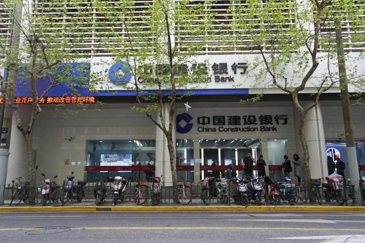 """In this April 13, 2018, photo, customers mill outside an automated bank in Shanghai. The outlet opened by Beijing-based China Construction Bank has been dubbed China's first """"unmanned bank"""" and is equipped with face-scanning software, a virtual reality room and talking robots. (AP Photo/Dake Kang)"""