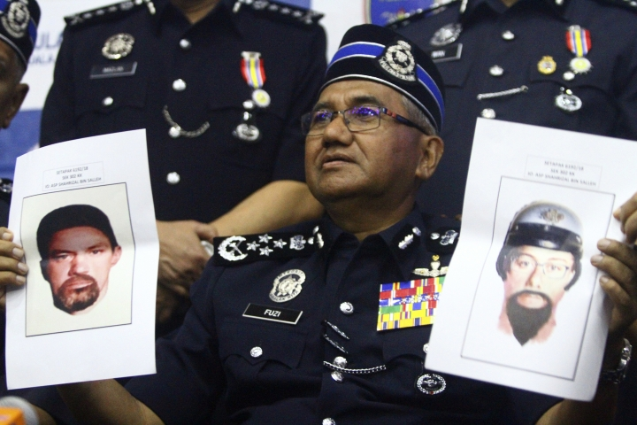 Inspector General of Royal Malaysian Police Mohamad Fuzi Harun shows off two images of suspects of killing of a Palestinian man during a press conference in Kuala Lumpur, Malaysia, Monday, April 23, 2018. Malaysian police said Sunday that an investigation was underway into the gunning down of the 34-year-old Palestinian al-Batsh a day earlier and gave assurances that security was being beefed up in the country following recent high-profile assassinations. (AP Photo)