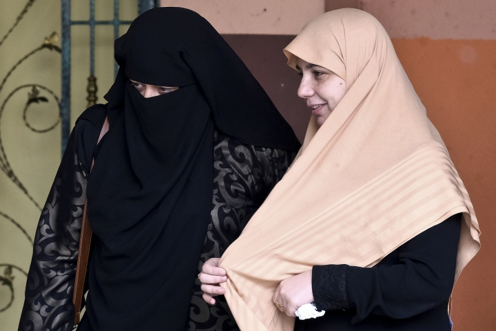 Enaas al-Batsh, right, wife of killed Palestinian Fadi al-Batsh, walks out of a hospital's morgue in Selayang, Malaysia, Monday, April 23, 2018. Malaysian police said Sunday that an investigation was underway into the gunning down of the 34-year-old Palestinian al-Batsh a day earlier and gave assurances that security was being beefed up in the country following recent high-profile assassinations. (AP Photo/Sadiq Asyraf)