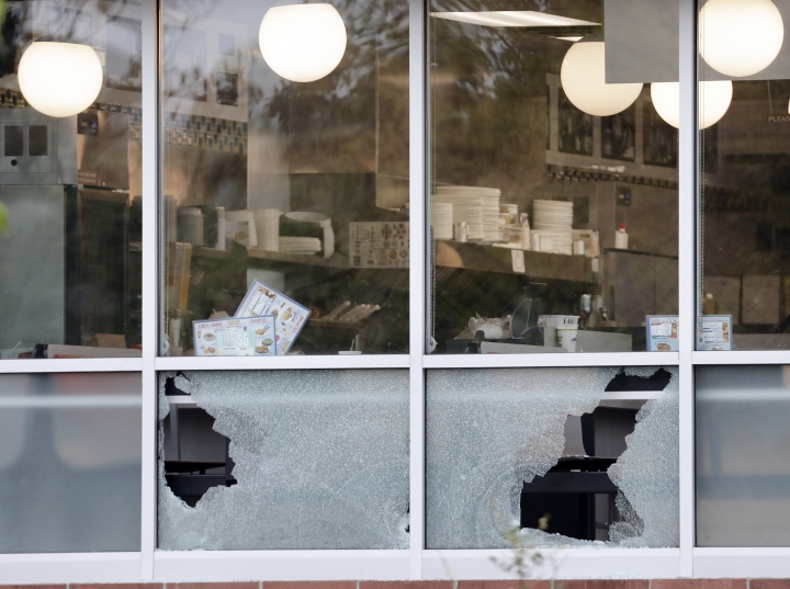 Menus sit on tables next to windows shot out at a Waffle House restaurant Sunday, April 22, 2018, in Nashville, Tenn. At least four people died after a gunman opened fire at the restaurant early Sunday. (AP Photo/Mark Humphrey)
