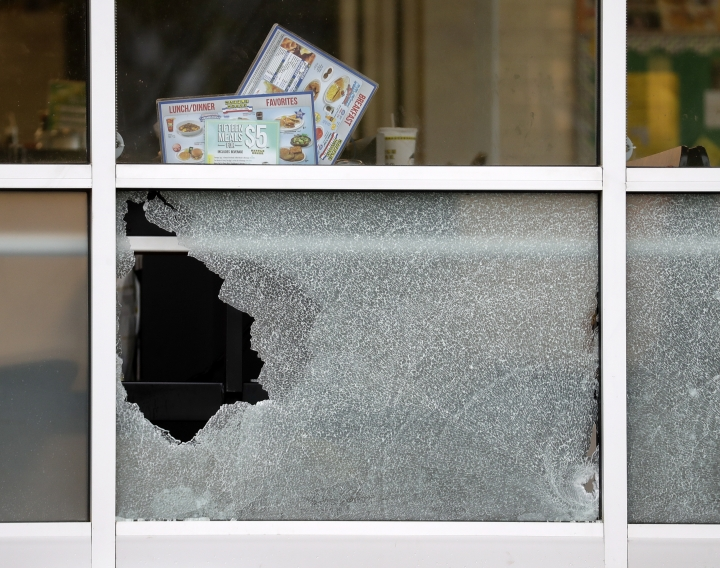 Menus and a cup sit on a table next to a window shot out at a Waffle House restaurant Sunday, April 22, 2018, in Nashville, Tenn. At least four people died after a gunman opened fire at the restaurant early Sunday. (AP Photo/Mark Humphrey)