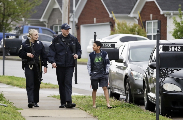 Nashville police officers talk to a boy as they search a neighborhood near a Waffle House restaurant Sunday, April 22, 2018, in Nashville, Tenn. At least four people died after a gunman opened fire at the restaurant early Sunday. (AP Photo/Mark Humphrey)