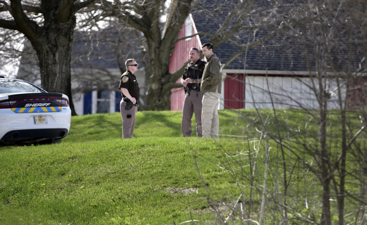 Tazewell County Sheriff's deputies talk with an unidentified man at the driveway of a home, Sunday, April 22, 2018, outside of Morton, Ill., where the extended family lives of Travis Reinking, who is the suspect in the fatal shooting that occurred at a Waffle House restaurant earlier in the day in Nashville, Tenn. (Fred Zwicky/Journal Star via AP)