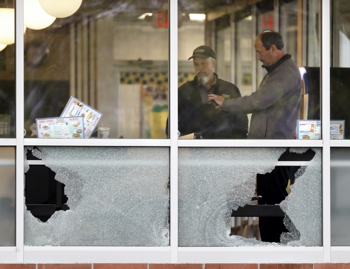 People look over an area near a window shot out at a Waffle House restaurant Sunday, April 22, 2018, in Nashville, Tenn. Several people died after a gunman opened fire at the restaurant early Sunday. (AP Photo/Mark Humphrey)
