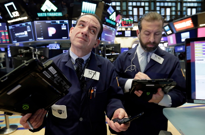 Traders Tommy Kalikas, left, and Greg Mulligan work on the floor of the New York Stock Exchange, Monday, April 23, 2018. U.S. stocks are mixed Monday morning as health care and industrial companies make gains and energy companies slip with oil prices. (AP Photo/Richard Drew)