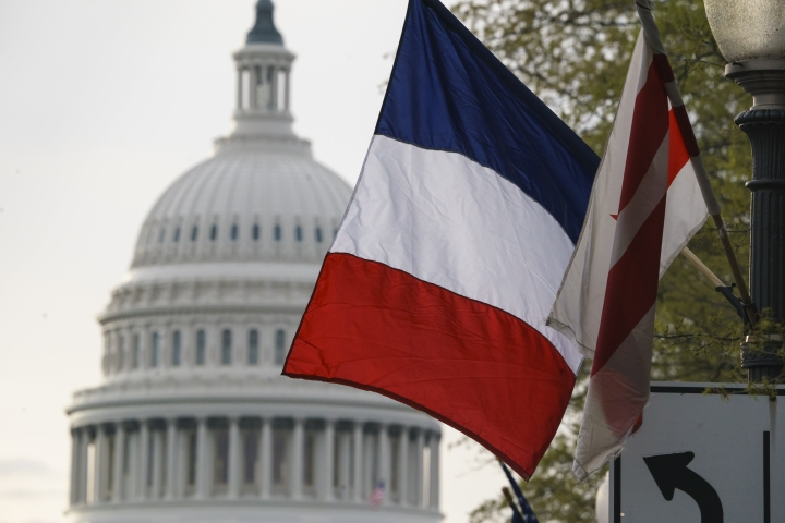 The French flag, along with the American flag and the flag of the District of Columbia, is seen with the U.S. Capitol in the distance in advance of French President Emmanuel Macron's Washington arrival for a state visit, Monday, April 23, 2018. Macron will address Congress this week after meeting with President Donald Trump. (AP Photo/J. Scott Applewhite)