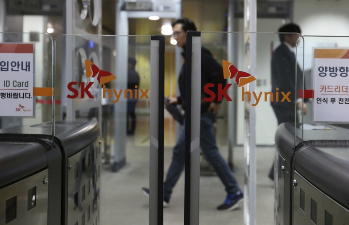 In this Monday, April 23, 2018 photo, people pass by the logos of SK Hynix Inc. at its office in Seongnam, South Korea. SK Hynix Inc. on Tuesday, April 24, says its first-quarter net profit has surged 64 percent over a year earlier thanks to robust memory chip prices. (AP Photo/Ahn Young-joon)