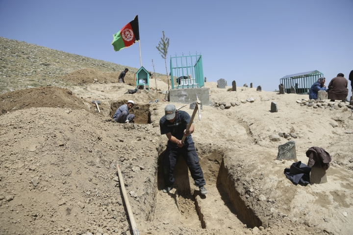 Afghan men prepare the graves for the victims of Sunday's suicide attack at a voter registration center, in Kabul, Afghanistan, Monday, April 23, 2018. Taliban attacks in western Afghanistan killed 14 soldiers and policemen on Monday as residents in the capital, Kabul, prepared for the funerals of those killed in the horrific bombing by the Islamic State group on a voter registration center that left at least 57 dead the previous day. (AP Photo/Rahmat Gul)