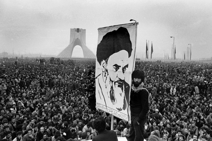 FILE- In this Dec. 10, 1978 file photo of exiled Muslim leader Ayatollah Khomeini overshadows huge anti-Shah demonstration at the Shahyad monument commemorating 25 years of the monarch's rule and symbol of his power, in Tehran, Iran. The discovery in Iran of a mummified body near the site of a former royal mausoleum has raised speculation it could be the remains of the late Reza Shah Pahlavi, founder of the Pahlavi dynasty. (AP Photo/Michel Lipchitz, File)