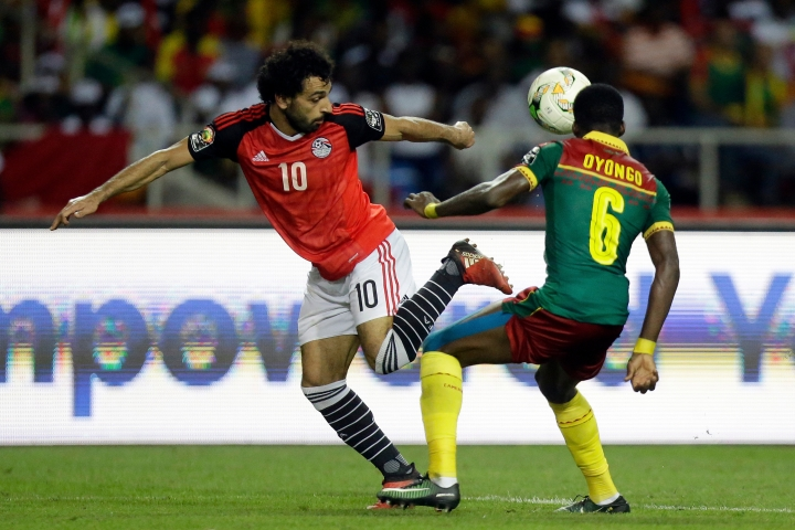 FILE- In this Sunday, Feb. 5, 2017 file photo, Egypt's Mohamed Salah, left, controls the ball in front of Cameroon's Ambroise Oyongo during the African Cup of Nations final soccer match between Egypt and Cameroon at the Stade de l'Amitie, in Libreville, Gabon. (AP Photo/Sunday Alamba, File)