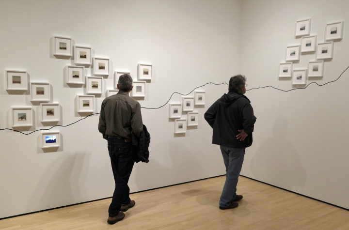 "In this March 15, 2018 photo, two men look at the conceptual project ""The People's View"" by Dutch artist Rein Jelle Terpstra that is part of the exhibit, ""The Train: RFK's Last Journey,"" at the San Francisco Museum of Modern Art in San Francisco. The photographs taken by bystanders, are arranged on the wall by where they were taken on the route from New York City to Washington. (AP Photo/Eric Risberg)"