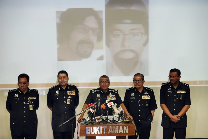 Malaysian National police chief Mohamad Fuzi Harun, center, speaks during a press conference in Kuala Lumpur, Malaysia, Wednesday, April 25, 2018. Malaysian police have released a photo of one of the two assailants who gunned down a Palestinian engineer this past weekend, and say the duo could still be in the country. (AP Photo/Vincent Thian)