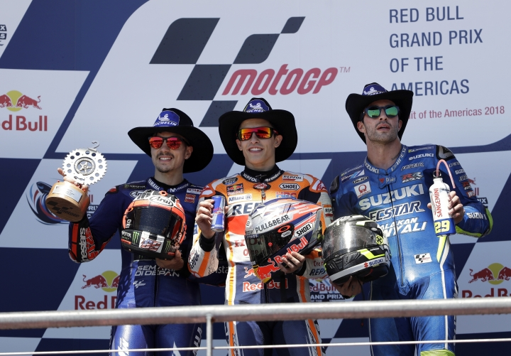From left to right, Maverick Vinales, of Spain; Marc Marquez, also of Spain; and Andrea Iannone, of Italy, celebrate their wins in the Grand Prix of the Americas motorcycle race at the Circuit of the Americas in Austin, Texas, Sunday, April 22, 2018. Vinales finished second behind winner Marquez with Iannone finishing in third. (AP Photo/Eric Gay)