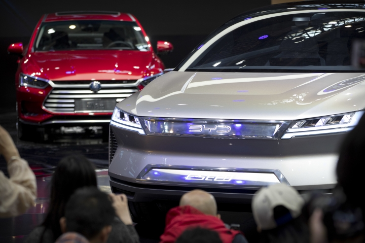 Attendees take photos of the E-SEED electric concept car during a press conference by Chinese automaker BYD at the China Auto Show in Beijing, Wednesday, April 25, 2018. Auto China 2018, the industry's biggest sales event this year, is overshadowed by mounting trade tensions between Beijing and U.S. President Donald Trump, who has threatened to hike tariffs on Chinese goods including automobiles in a dispute over technology policy. (AP Photo/Mark Schiefelbein)