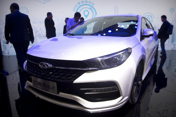 Attendees look at the Arrizo GX by Chinese automaker Chery after a press conference at the China Auto Show in Beijing, Wednesday, April 25, 2018. Auto China 2018, the industry's biggest sales event this year, is overshadowed by mounting trade tensions between Beijing and U.S. President Donald Trump, who has threatened to hike tariffs on Chinese goods including automobiles in a dispute over technology policy. (AP Photo/Mark Schiefelbein)