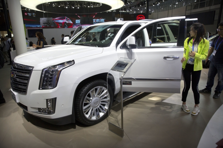 Visitors look at a Cadillac Escalade at the China Auto Show in Beijing, Wednesday, April 25, 2018. Auto China 2018, the industry's biggest sales event this year, is overshadowed by mounting trade tensions between Beijing and U.S. President Donald Trump, who has threatened to hike tariffs on Chinese goods including automobiles in a dispute over technology policy. (AP Photo/Mark Schiefelbein)