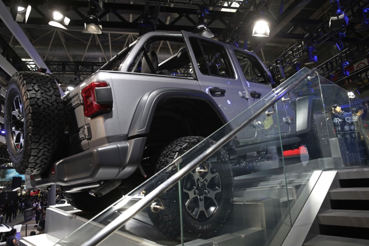 A journalist, right, is reflected on a glass panel as he film the Jeep Wrangler Limited on display at the China Auto Show during the media day in Beijing, Wednesday, April 25, 2018. Volkswagen and Nissan have unveiled electric cars designed for China at a Beijing auto show that highlights the growing importance of Chinese buyers for a technology seen as a key part of the global industry's future. (AP Photo/Andy Wong)