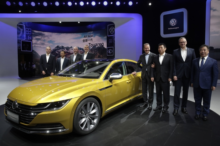 Herbert Diess, CEO of Volkswagen, fourth from right, poses with officials and the newly unveiled Volkswagen CC car model during the media day of the China Auto Show in Beijing, Wednesday, April 25, 2018. Volkswagen and Nissan have unveiled electric cars designed for China at a Beijing auto show that highlights the growing importance of Chinese buyers for a technology seen as a key part of the global industry's future. (AP Photo/Andy Wong)