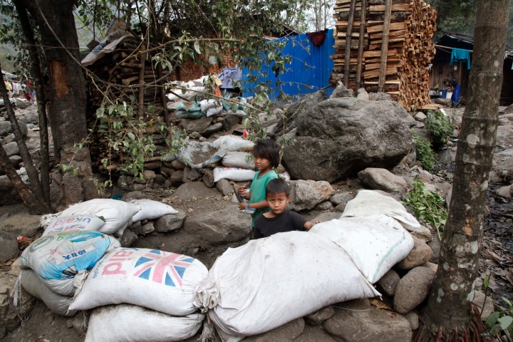 In this March 19, 2018 photo, refugee children play in a makeshift bomb-shelter made with sandbags at Woi Chyai camp for refugees close to Laiza, northern Kachin state, Myanmar. Bomb shelters were built close to refugee camps after the Myanmar shells fall near refugee camps in December, 2017, injuring civilians. (AP Photo/Esther Htusan)