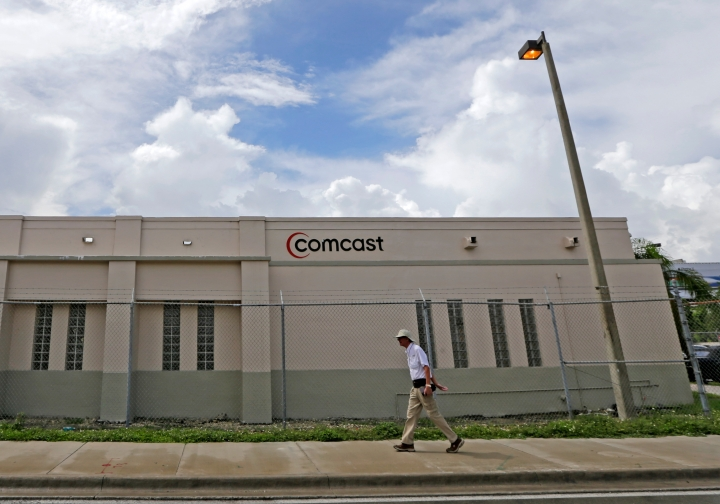 FILE- In this Oct. 12, 2017, file photo a pedestrian walks by a Comcast Service Center, in Miami. Comcast Corp. reports earnings Wednesday, April 25, 2018. (AP Photo/Alan Diaz, File)