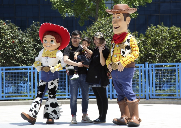 A family poses for a photo with characters from the Toy Story movies during the grand opening of Toy Story Land at Shanghai Disneyland in Shanghai, China, Thursday, April 26, 2018. Walt Disney Co. stressed its deep China connections as it opened an extension of Shanghai's $5.5 billion Disney Resort on Thursday amid escalating tensions over trade and technology between Beijing and Washington. (AP Photo)